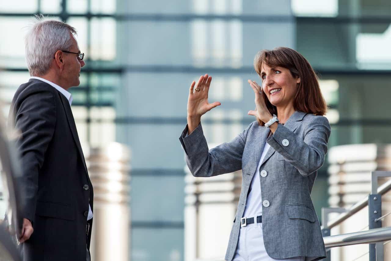 Business Portrait Gesprächssituation Geschäftsfrau und Geschäftsmann vor Glas-Stahl-Wand