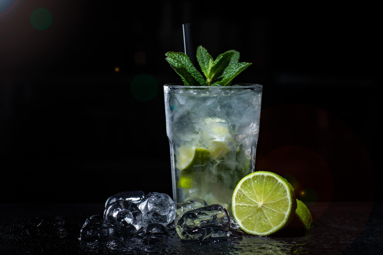 Mojito mit Limone und Eiswürfeln vor schwarzem Hintergrund