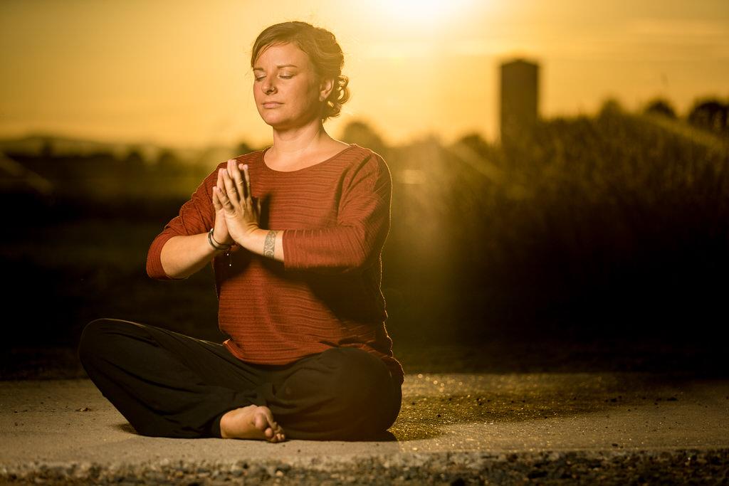 Yoga-Lehrer im Schneidersitz im Sonnenuntergang