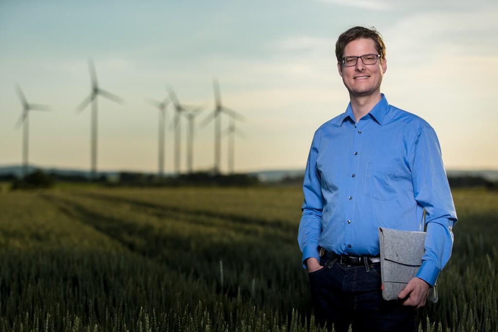 Business-Portrait Ingenieur vor Windrädern